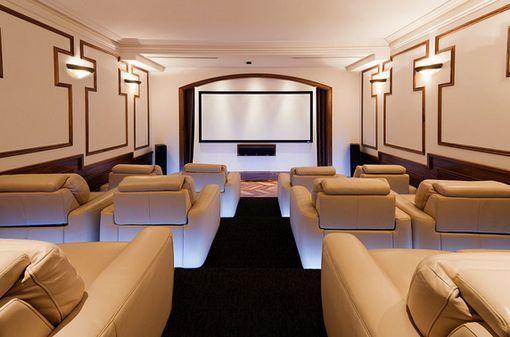Sala de cine en casa con sillones relax