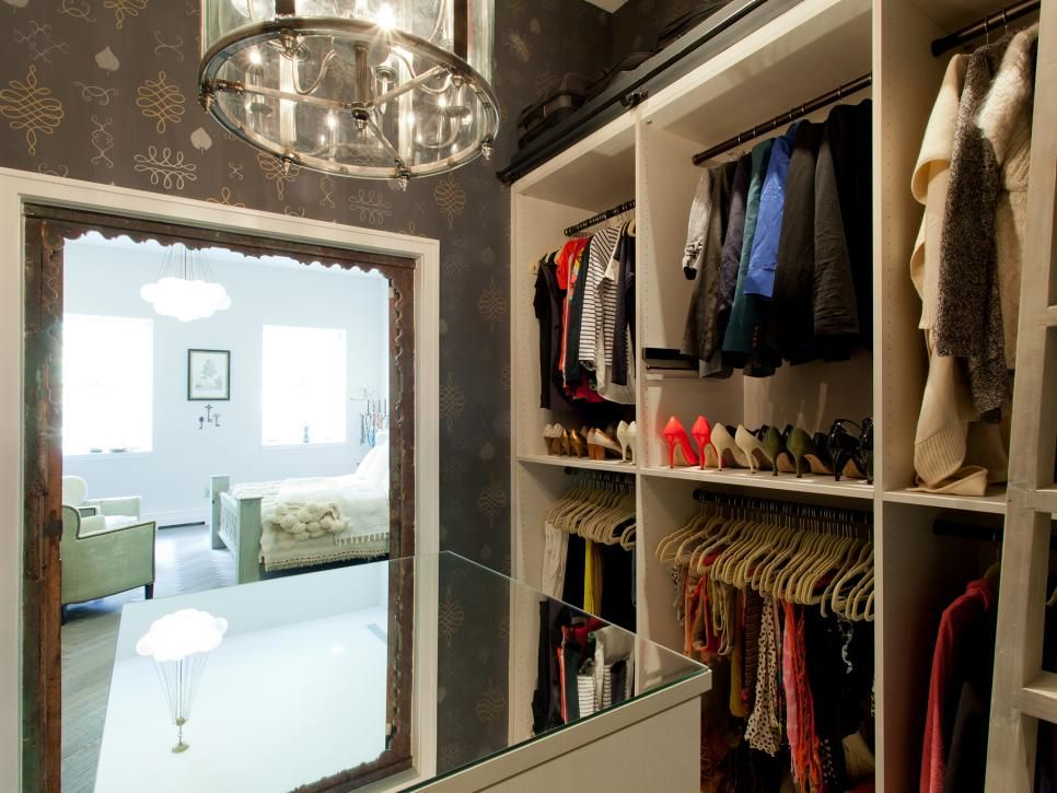 "Genevieve Gorder designed her dressing area with an elegant chandelier, doors imported from Morocco and plenty of shelves for clothes and shoes. A large mirrored island reflects the light from a sparkling chandelier throughout the plum-colored space, as seen on HGTV's ""Genevieve's Renovation."""