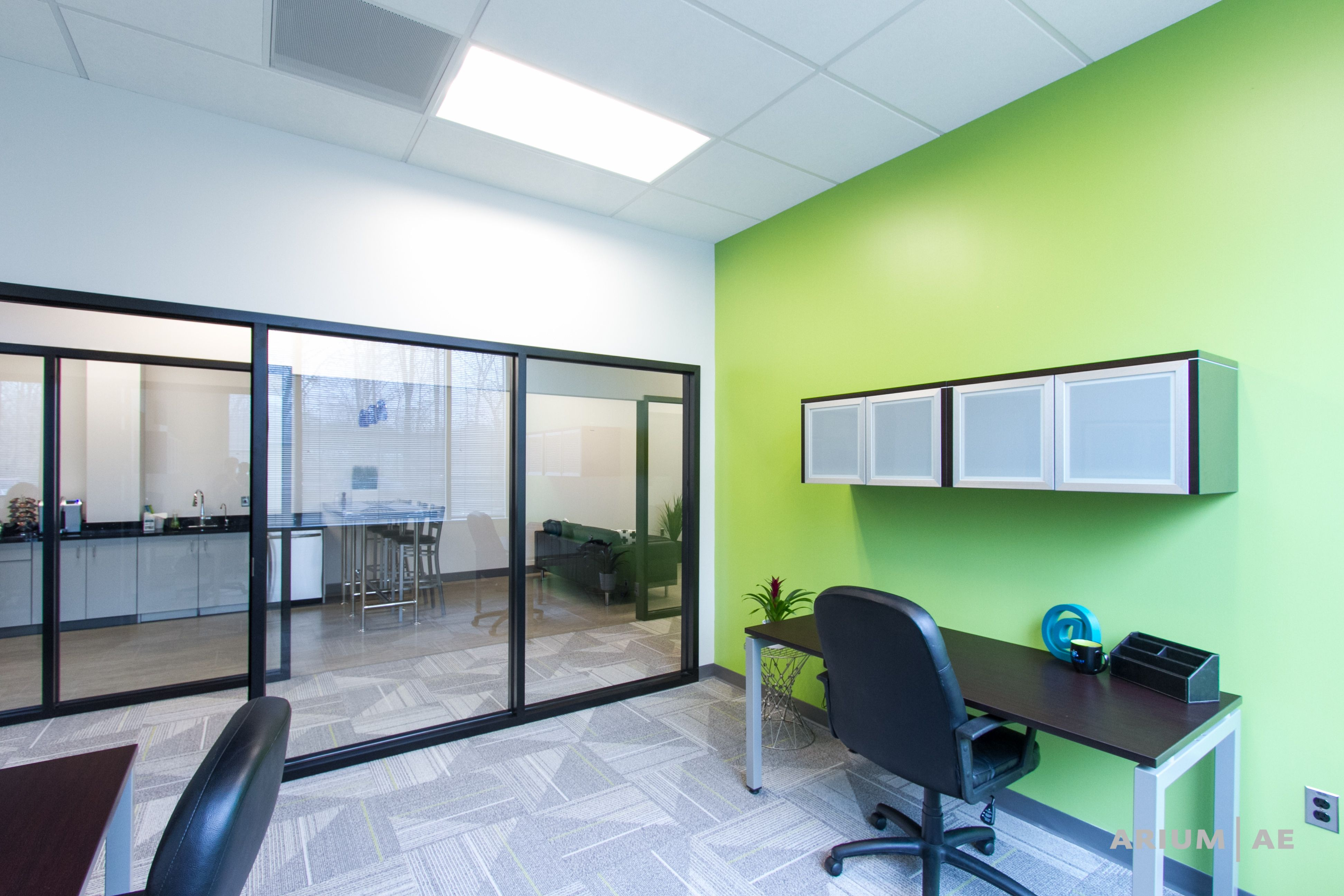 Two person office with green accent wall overhead storage black framed glass walls and view into break and game area