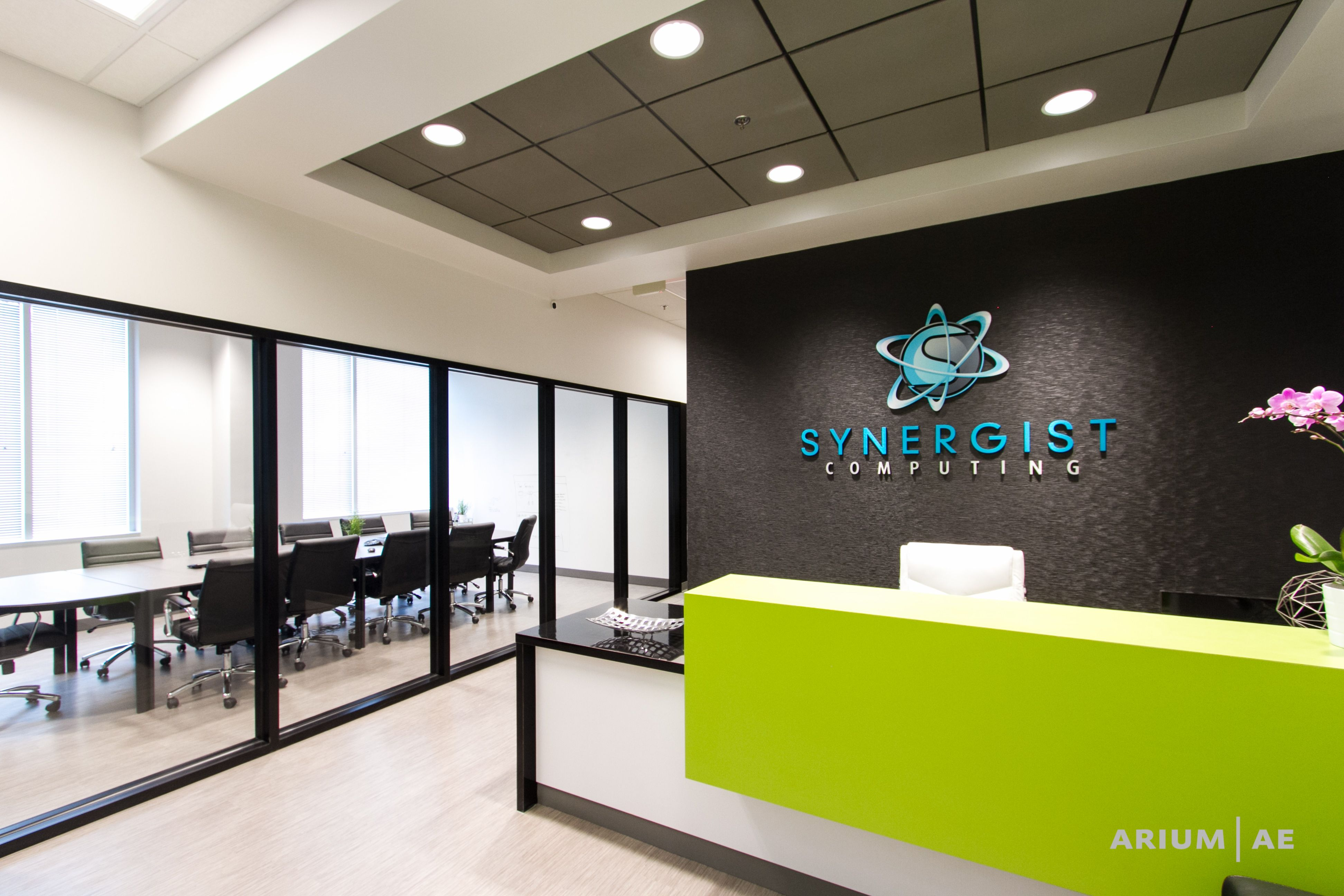Office Reception Area With Custom Reception Desk Green Accents Black Framed Glass Walls With View Into Conference Area Recepcao