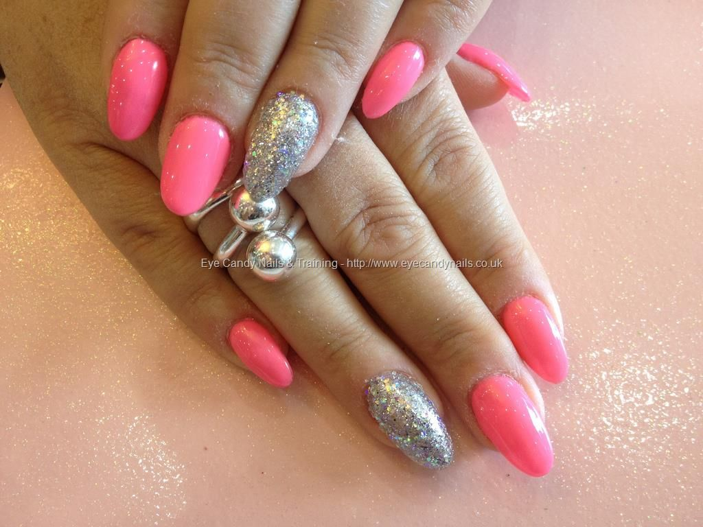 Acrylic nails with pink gel polish and silver glitter on ring finger ...