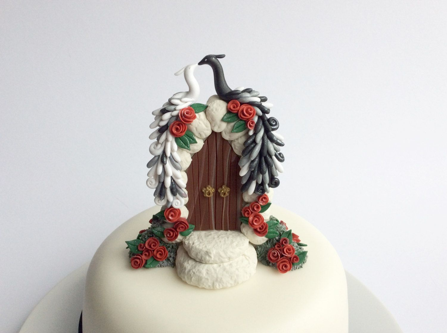 Peacock wedding cake topper in black and white with red roses