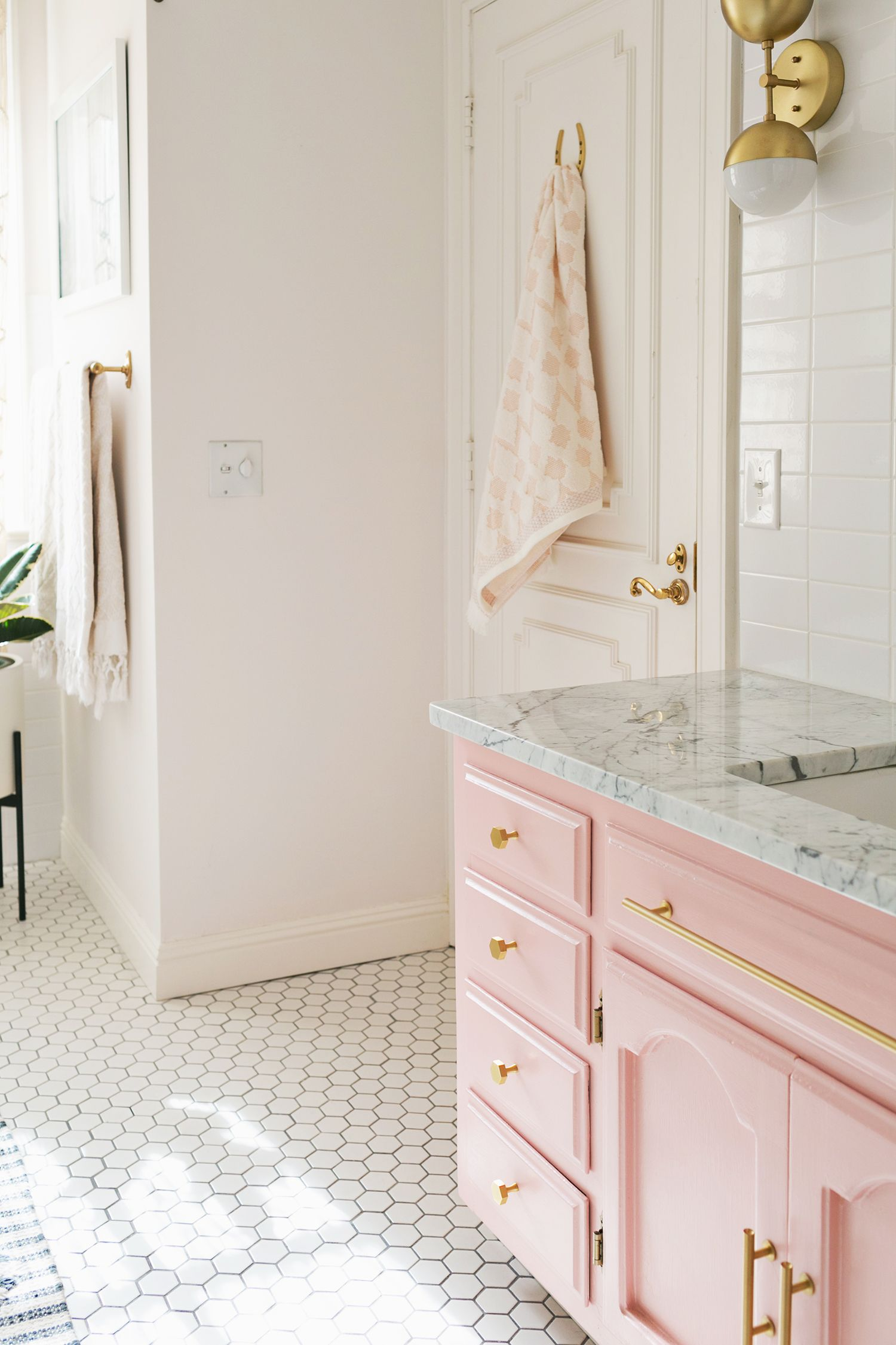 blush cabinets marble bathroom gold fixtures white hexagon tile in bathroom