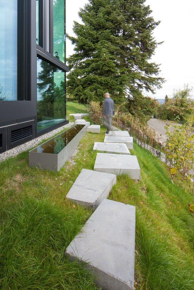 10 landscaping ideas for using stepping stones in your garden large concrete stepping stones line the side of this sloping yard making for an easy path
