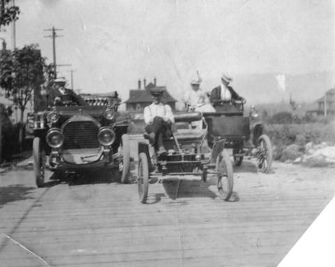 [Three early cars on a planked alley in the West End] - City of Vancouver Archives