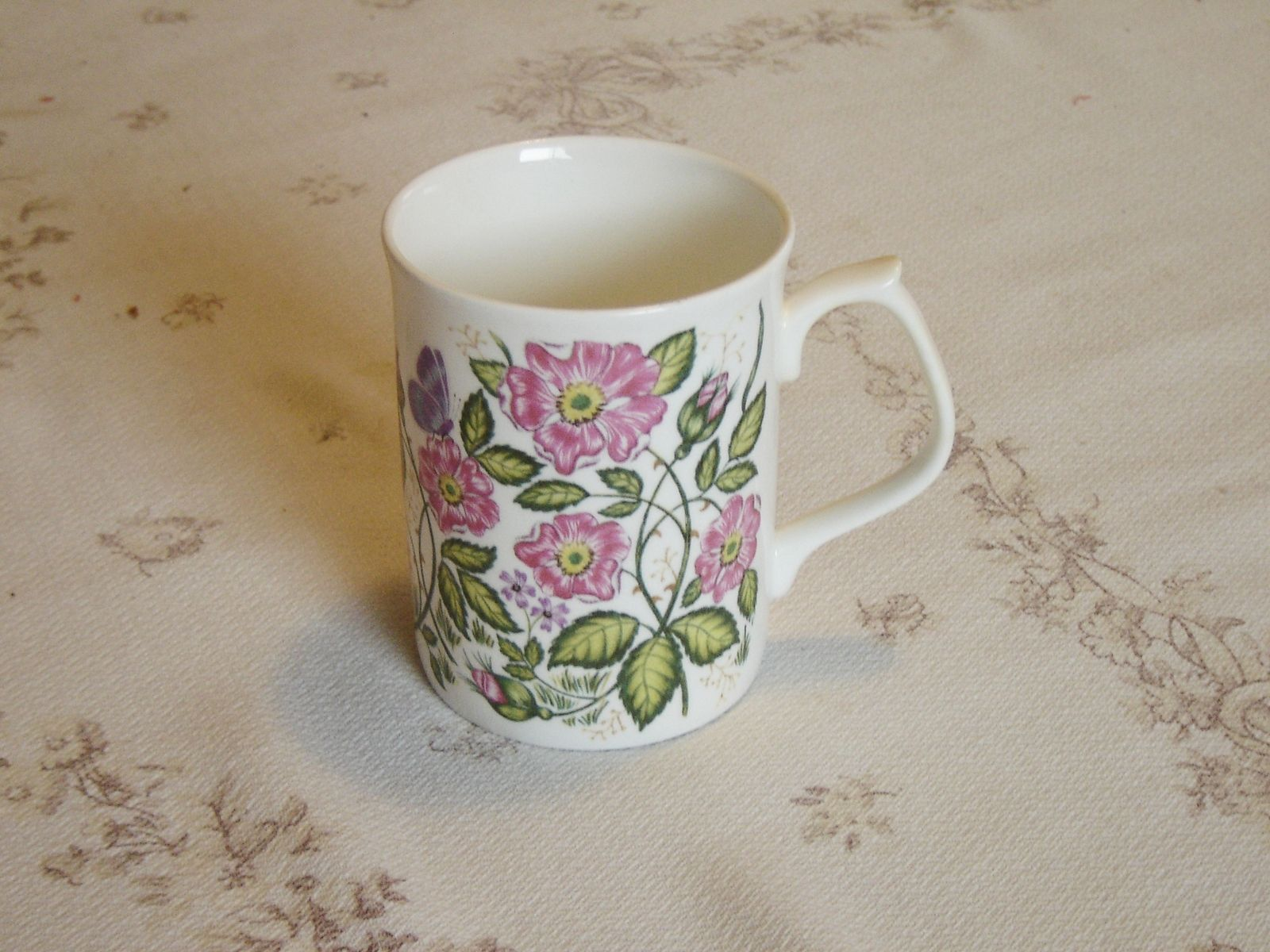 """Mug in a pink and purple floral display   This mug is 3 5/8"""" (9.2 cm) high x 2 7/8"""" (7.3 cm) at the brim   This mug is in near mint condition and doesn't appear to have been used as anything other than a collectible   Made of fine bone china from England by Jason"""