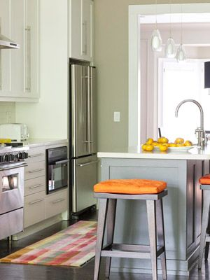Gray-green kitchen with orange accents
