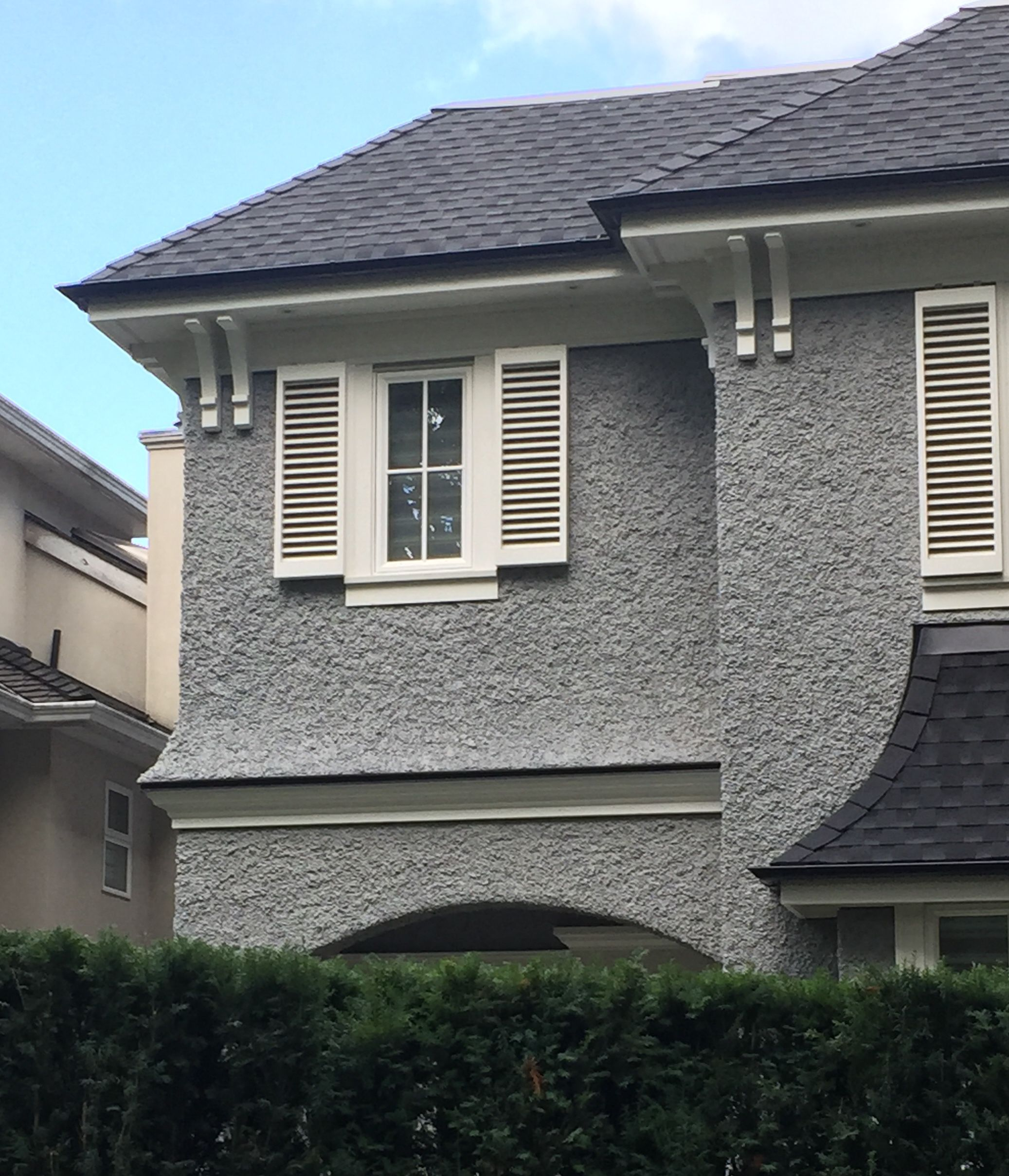 house colors grey stucco white windows and trim black roof gutters heavy slop stucco exterior