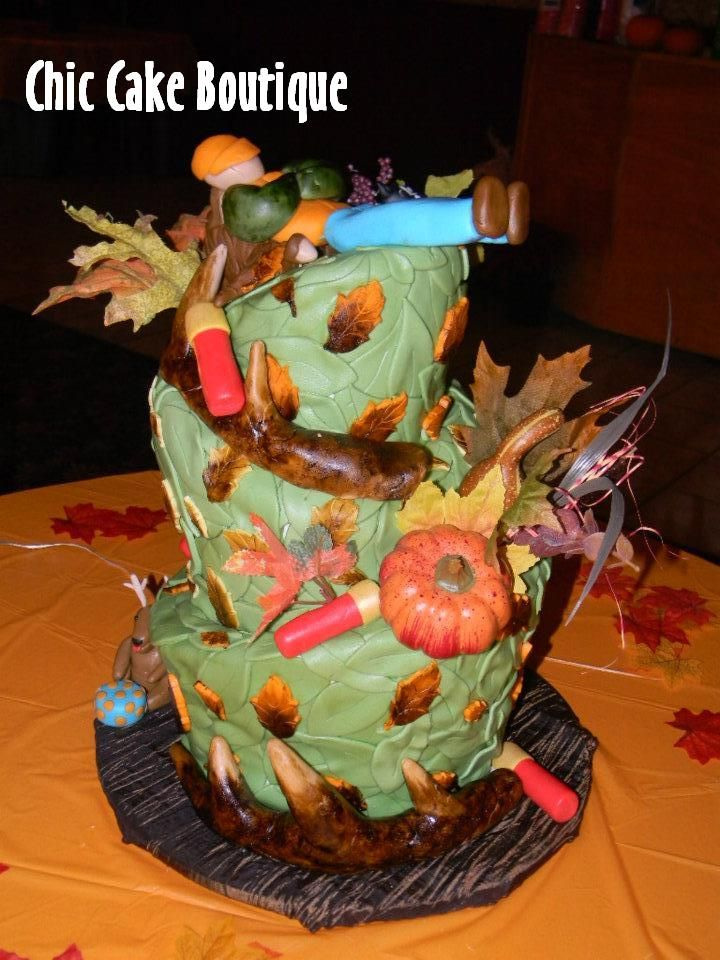 Hunting Cake..There is a sleeping hunter on the top with a deer on the bottom eating his cake! The tiers are decorated with fake flowers, sugar leaves, sugar shotgun shells, and deer antlers!!!