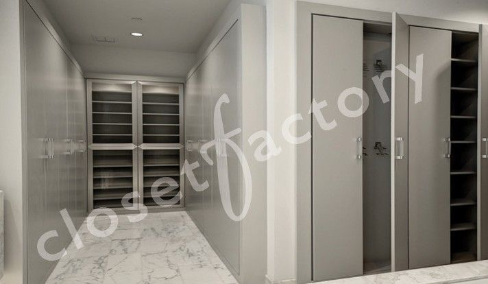 This sleek grey closet closet is a mirror image on both sides for a his and her closet.  The back wall has shoe shelves behind aluminum and reeded glass doors.