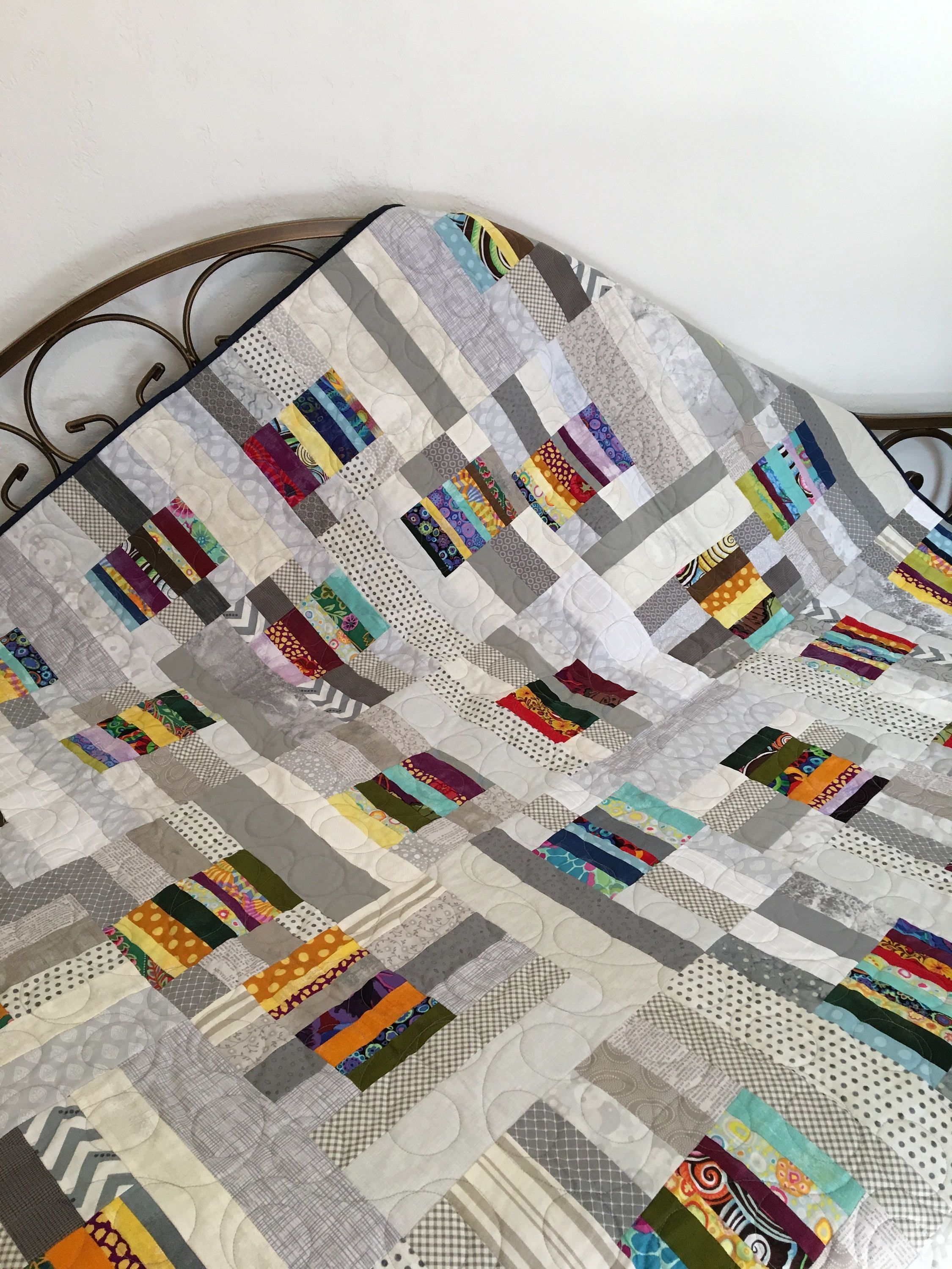 This is a gorgeous, modern quilt made from a variety of grey prints with pops of colored pieces. The back of this quilt features navy blue Grunge. All over quilted in a circular loop pattern. Quilt measures approximately 60 inches square which would work well as a baby quilt, lap #MasculineBedding #modernquiltingdesigns