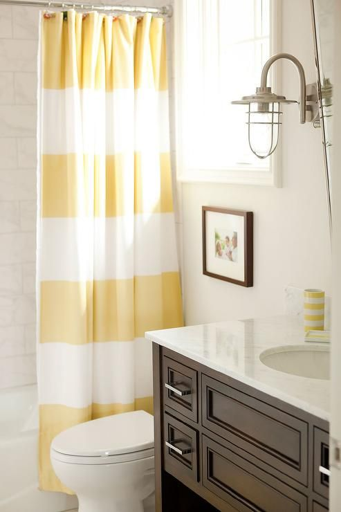 Yellow And Brown Bathroom Features A Dark Washstand Topped With White Marble Under