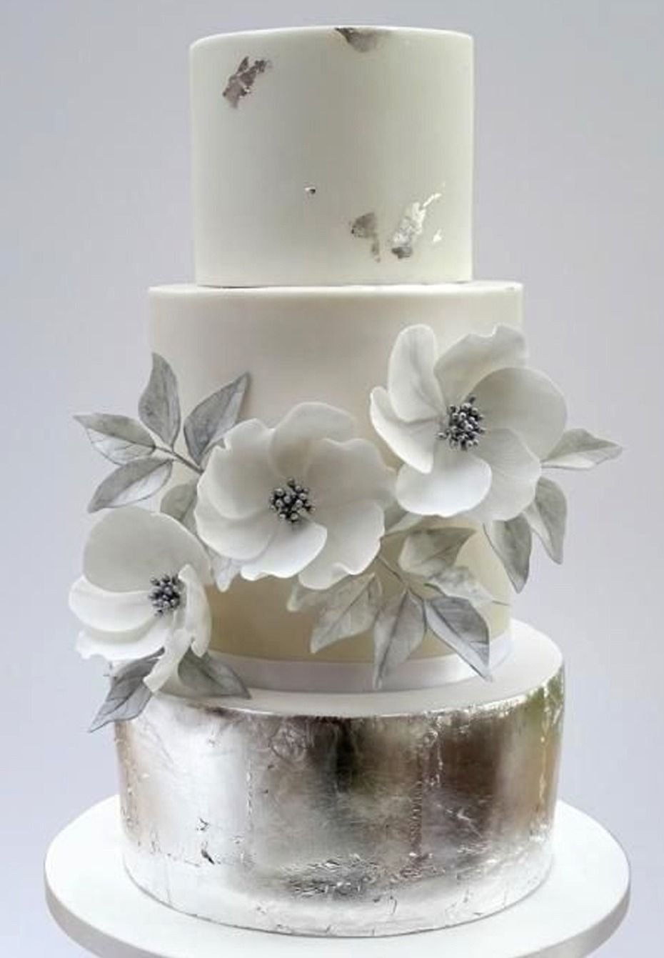 White and silver wedding cake with anemones flower weddingcakes