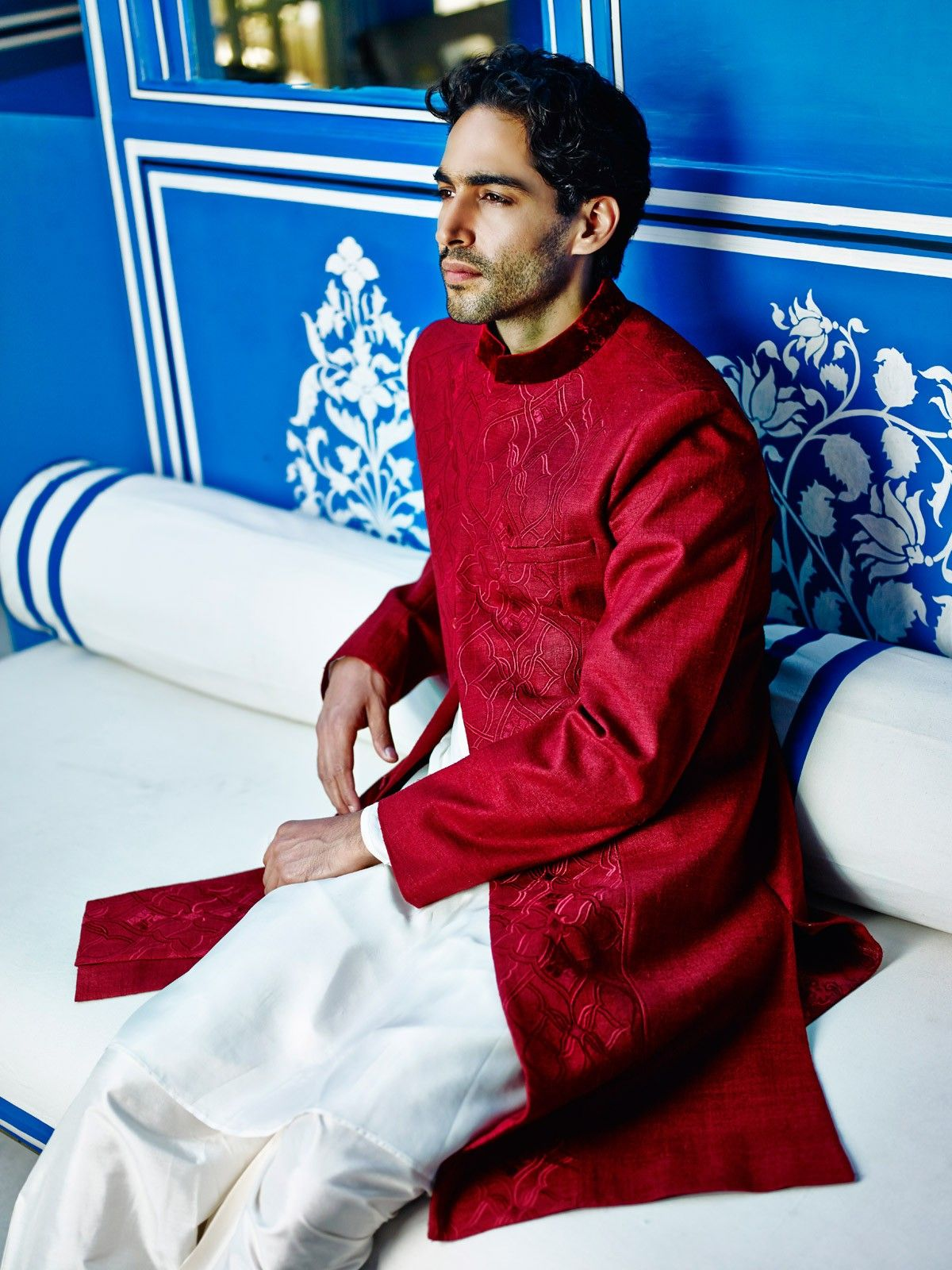 A traditional red sherwani is accentuated with subtle embroidery and velvet details to uplift the look. Team it with an off-white salwar and it's a great look for the wedding festivities.