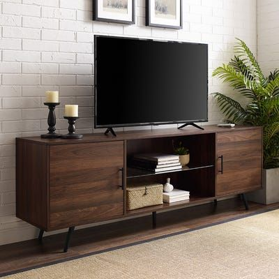 Take your living room to the next level with this stylish 70-inch TV stand. Made with metal tapered legs, sleek metal handles, and a center glass shelf for a mid century modern appearance. This high-grade MDF entertainment center creates additional storage space in your home for media, electronics, accessories, books, or décor. Use as a TV stand in your living room, a storage cabinet in your bedroom, or a buffet in your kitchen or dining room. Including two side cabinets for closed storage ...