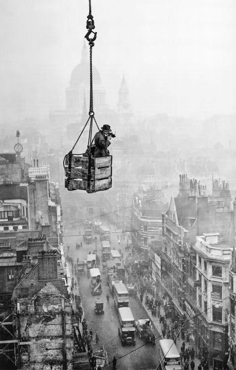R J Salmon dangles in a crate suspended from a crane to take an aerial shot of Fleet Street, London.  (Fox Photos)