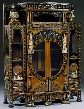 CARLO BUGATTI vitrine centred by two glazed doors beneath open shelf and three small frieze drawers, flanked by two glazed side cupboards each with small drawers above and below, the whole intricately composed of columns, turned galleries and small shelves, elaborately decorated throughout with moorish motifs and beaten and pierced copper roundels, various woods inlaid with bone and yellow and grey metal and hung with knotted silk tassels, elaborate key, c. 1900, 65 in. high, 49 in. wide