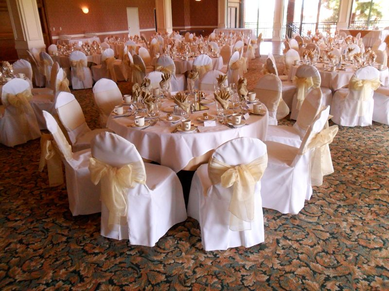 White Chair Covers Available For Rent With Yellow Gold Bows In