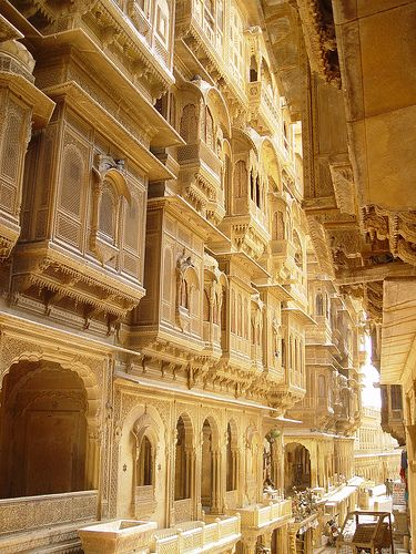 """Located way out in India's Thar Desert in Rajasthan, the """"Golden City"""" of Jaisalmer gets its color from buildings made of yellow sandstone (especially glowy at sunset). For centuries the city was an important post on camel routes from India to Central Asia – havelis like the one below are elaborate sandstone mansions built by wealthy merchants back in the Jaisalmer's trading heyday."""
