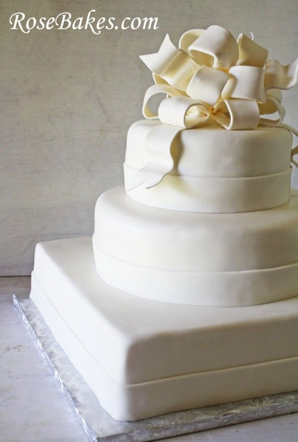 Simple and elegant all white wedding cake with poofy bow topper.