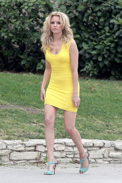 2338639e447 Elizabeth Banks struggles to ride a bicycle in a short yellow dress and  high heels as she films a scene for