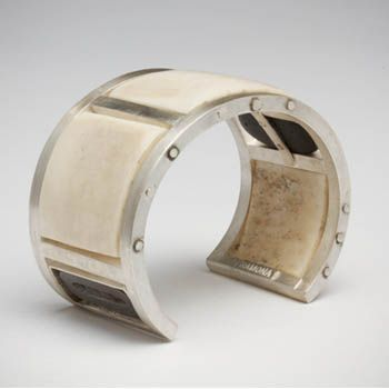 """Laurie Hall: Full Circle, Bracelet in sterling silver, bone, beach pebble and lead type piece. Bracelet frame by Ramona Solberg. 1 1/2"""" wide..."""