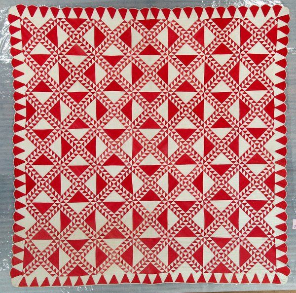 "Circa 1880 - Forty-nine 11"" blocks are made of two rows of alternating red and white triangles which cross in the center. There are larger alternating red and white triangles between the rows. The 3 1/2"" wide border is made of alternating pieced triangles. The 1/4"" white bias binding is stitched front to back. There are scalloped edges on three sides."