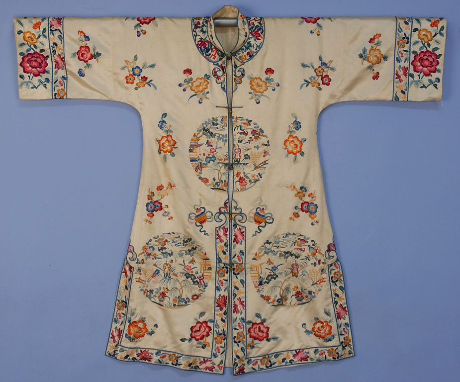 China silk embroidered robe, cream satin with vibrant satin stitch floral and figural rounds, figured silk lining and brass buttons, 20th c