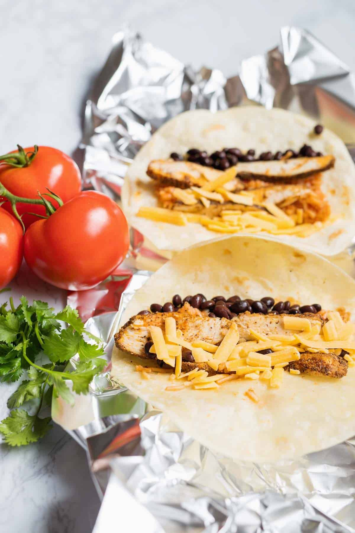 This Easy Chicken Burrito Recipe is a quick and easy dinner packed with tender chicken, black beans and Spanish rice that you can make now or freezer for later. via