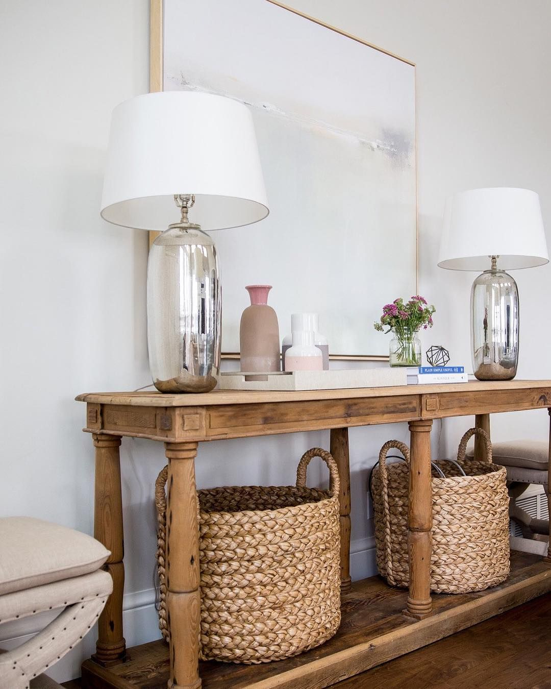 Another perfect entryway from studio mcgee so many details to beige x stools flank a reclaimed wood console table fitted with a shelf holding seagrass baskets and topped with mercury glass lamps placed on either side geotapseo Gallery