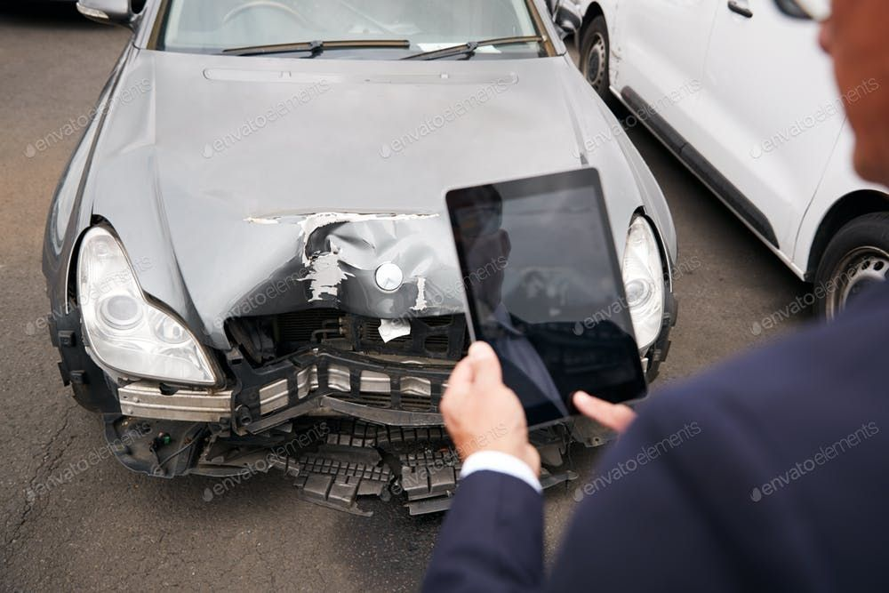 Insurance Loss Adjuster Taking Picture With Digital Tablet Of