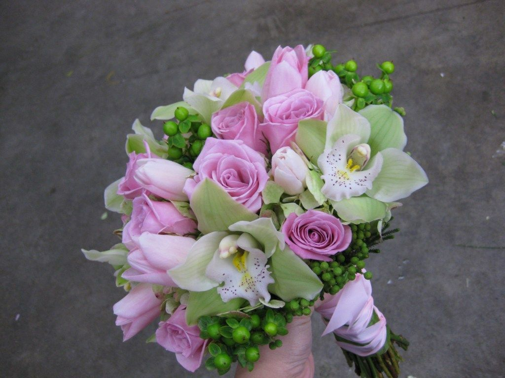 Bridal bouquet with pink roses, pink tulips, green cymbidium orchids, green hypericum