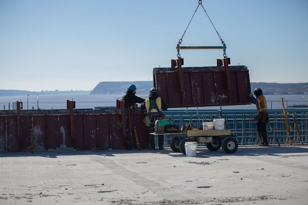 February 17, 2017 - Workers lower formwork that will help create the shape of concrete road barriers.