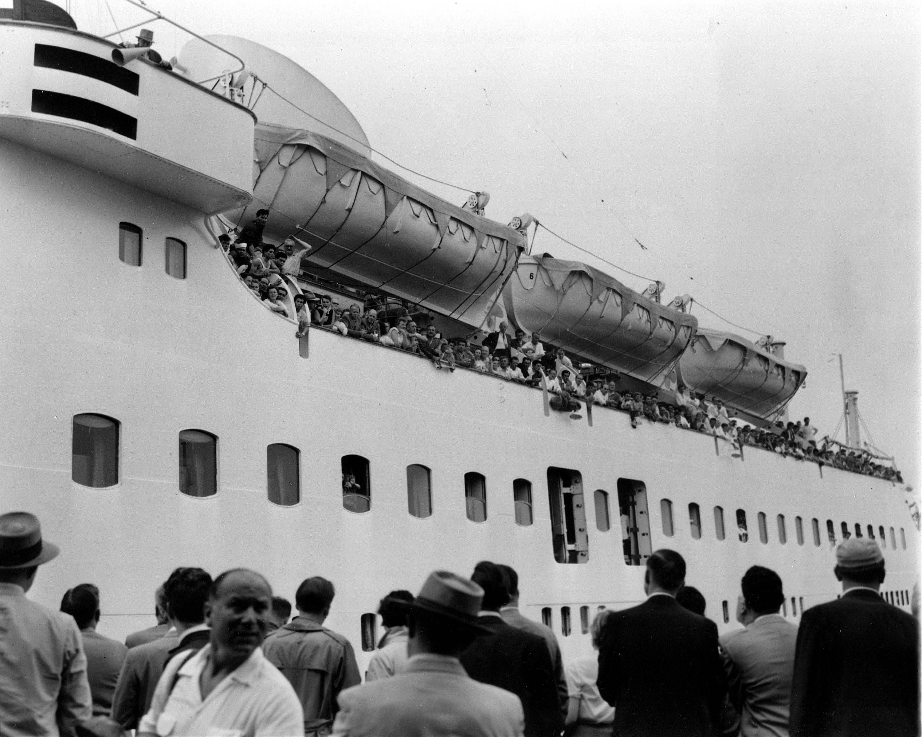 Surviving passengers of the Italian luxury liner Andrea Doria line the rail of the Swedish-American liner Stockholm as she pulls into North River Pier in New York, July 27, 1956. The Stockholm suffered a smashed bow after colliding with the Andrea Doria July 25.