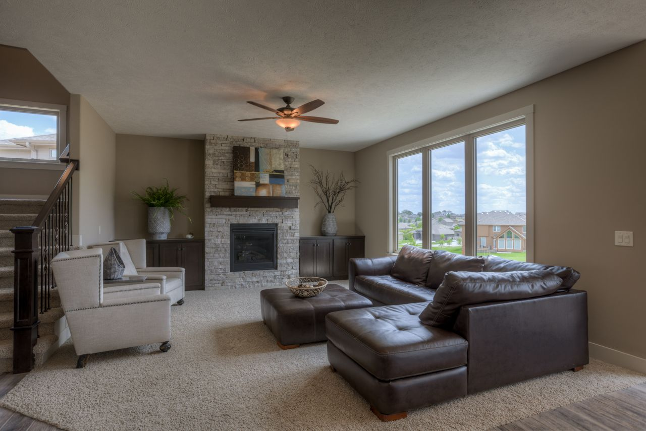 Great room with stone fireplace and wood mantle newport story w