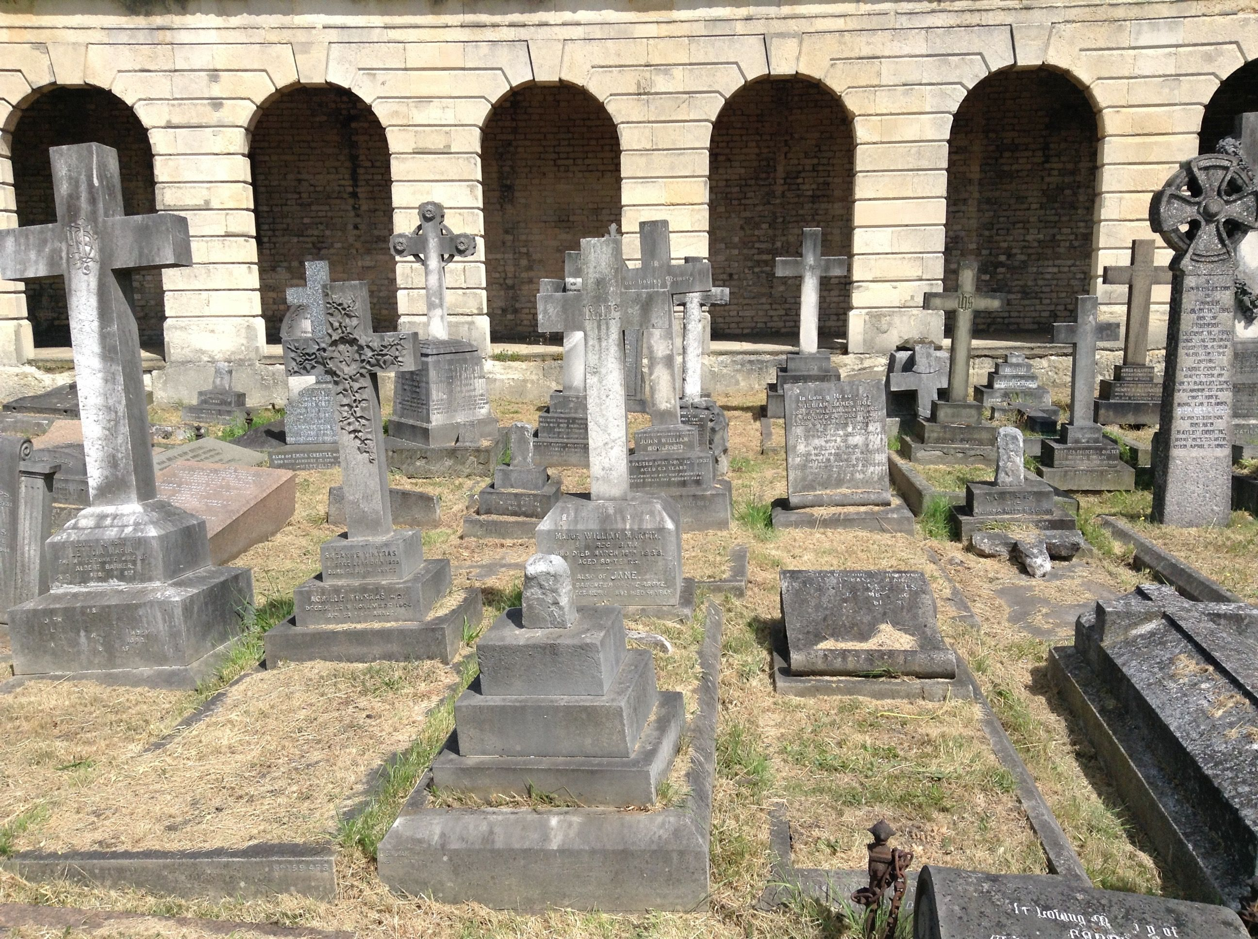 View of the numerous tombs in the circle of Brompton Cemetery, London, England, with the colonnades in the background.  Below the colonnades are catacombs which were originally conceived as a cheaper alternative burial to having a plot in the grounds of the cemetery. Unfortunately, the catacombs were not a success and only about 500 of the many thousands of places in them were sold.