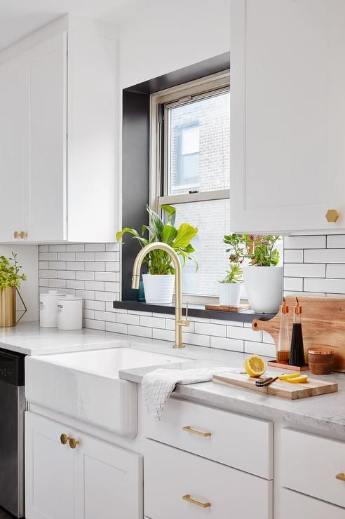 White And Gold Kitchen Features A Window Framed By A Black Windowsill Positioned Above A Farmhouse Sink W Kitchen Window Sill Kitchen Renovation Kitchen Marble