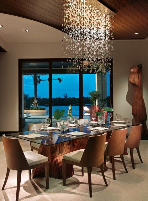 Tropical dining room design with glass top dining table and upholstered chairs and crystal dining room chandelier.