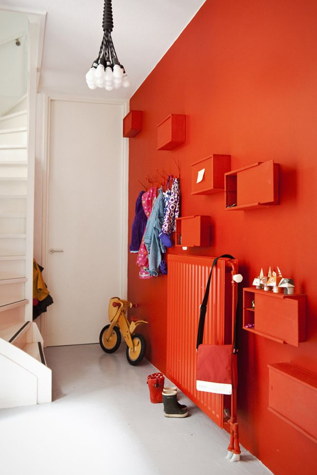 saturated feature wall of colour including hooks, radiator and shelving