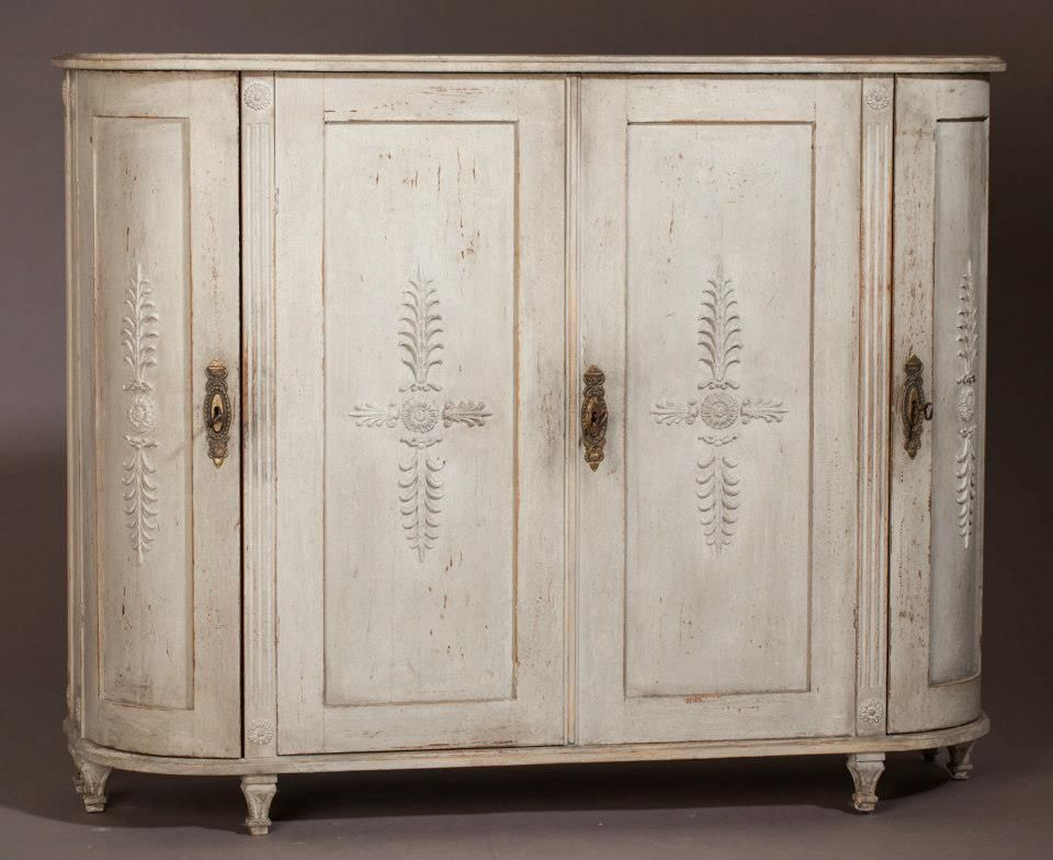 A Late Gustavian Swedish Sideboard with two curved side doors. Elegant carvings, old light grey paint surface. Original locks and keys. Circa 1820.