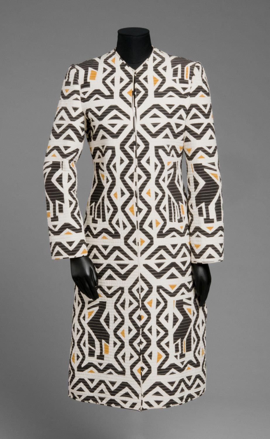 Woman's evening coat | Designer: Mary McFadden | United States, Spring-Summer 1987 | Black, tan and white printed quilted silk plain weave | This coat is from McFadden's 'Chapungo' collection inspired by Africa, where she lived for a number of years in the 1960's. The dramatic print features bird forms derived from the funerary totems of the Sakalava-Vezo people of Madagascar | The columnar coat is given a supple body by McFadden's signature narrow quilting | Philadelphia Museum of Art