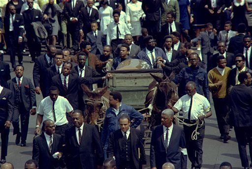A brace of plow mules draws the farm wagon bearing the casket of Dr. Martin Luther King, Jr., along the funeral procession route in Atlanta, Ga., April 9, 1968.