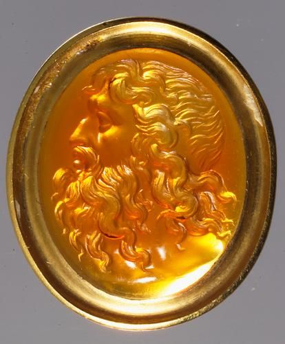 KHM Bilddatenbank — KHM Bilddatenbank. Kopf des Neptun Neuzeitlich,  18. Jh.  Karneol, hellorangefarben, klar, durchscheinend. In Goldfassung.  H. 1,11 cm, B. 0,93 cm, D. 0,17 cm