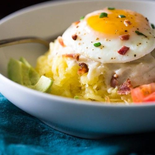 Dive into this delicious bowl of low-carb spaghetti squash topped with cauliflower Alfredo. bacon crumbles, and a tasty egg!
