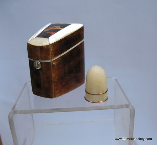 Mother-of pearl thimble, beehive shape, with two gilt bands. Housed on a velvet covered post inside a tortoishell mother -of-pearl banded case. English cir 1830. These items can be sold separately as the thimble may be older than the case.