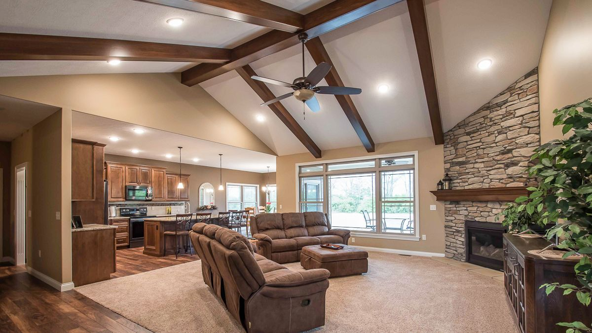 Great Room Of Allison Model Features Cathedral Ceilings With Wood Beams And Corner Floor To Ceiling Fireplace Natural Blend Ledge Stone