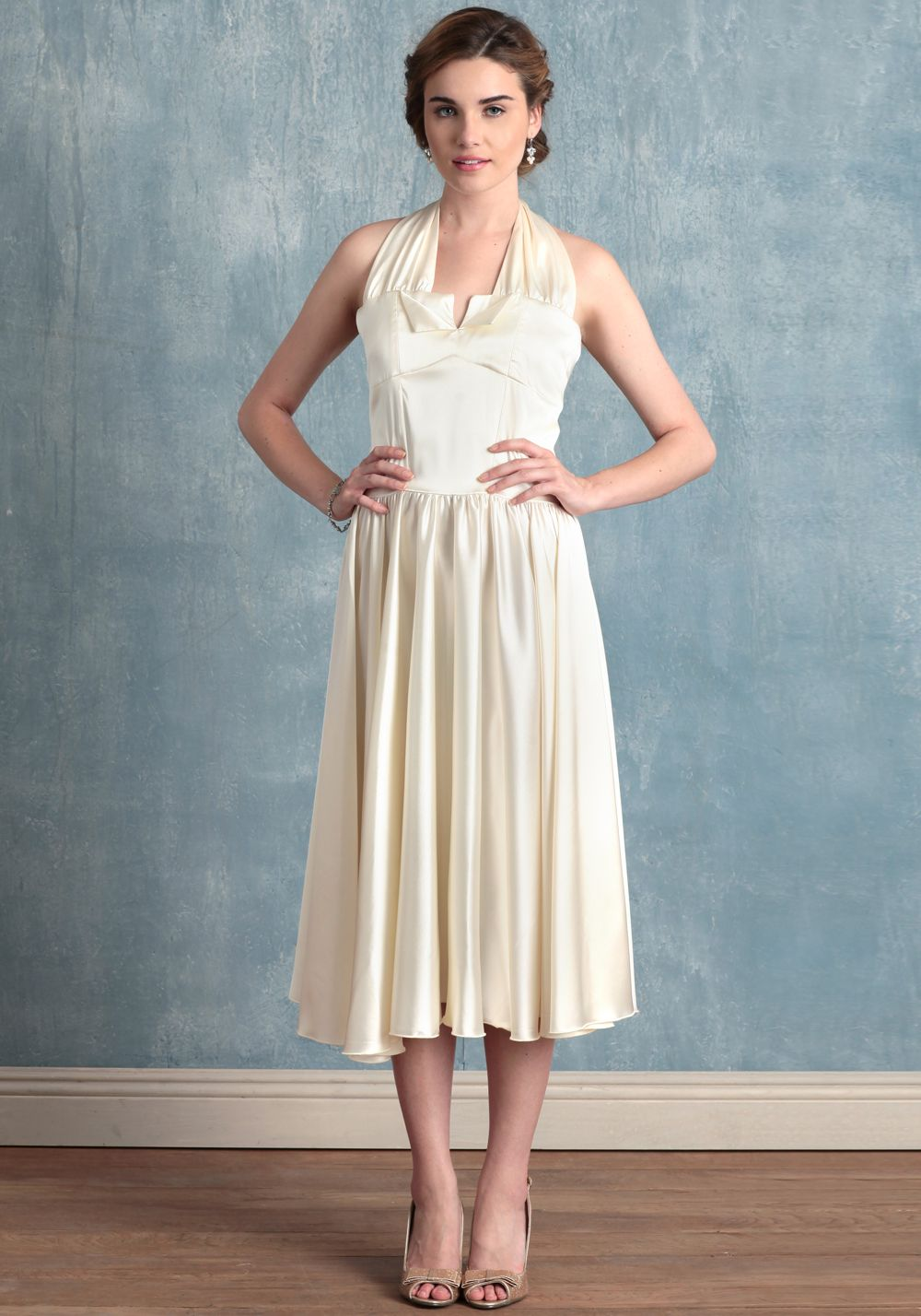 "Perfect for the vintage-loving bride, this cream satin wedding dress is polished with a sophisticated halter neck, a classic circle skirt for graceful movement, and a demure split neckline. Finished with delicate gathers at the waist for added fullness and a back zipper closure. Fully lined.  100% Polyester, Made in USA, 47"" length from top of shoulders, 34"" bust, 28"" waist, All measuremen..."