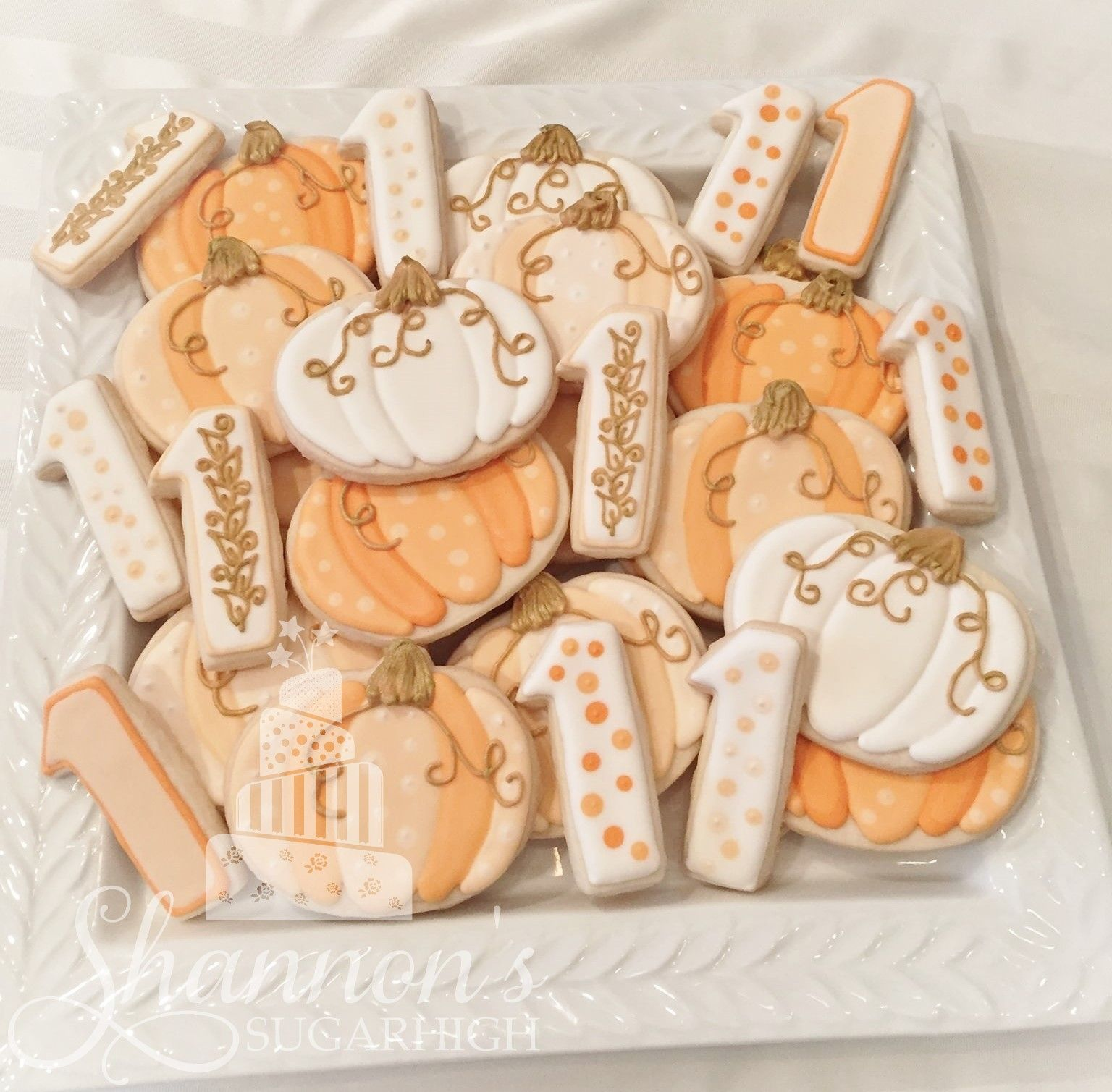 fall pumpkin cookies and number 1s in white gold and different shades of orange