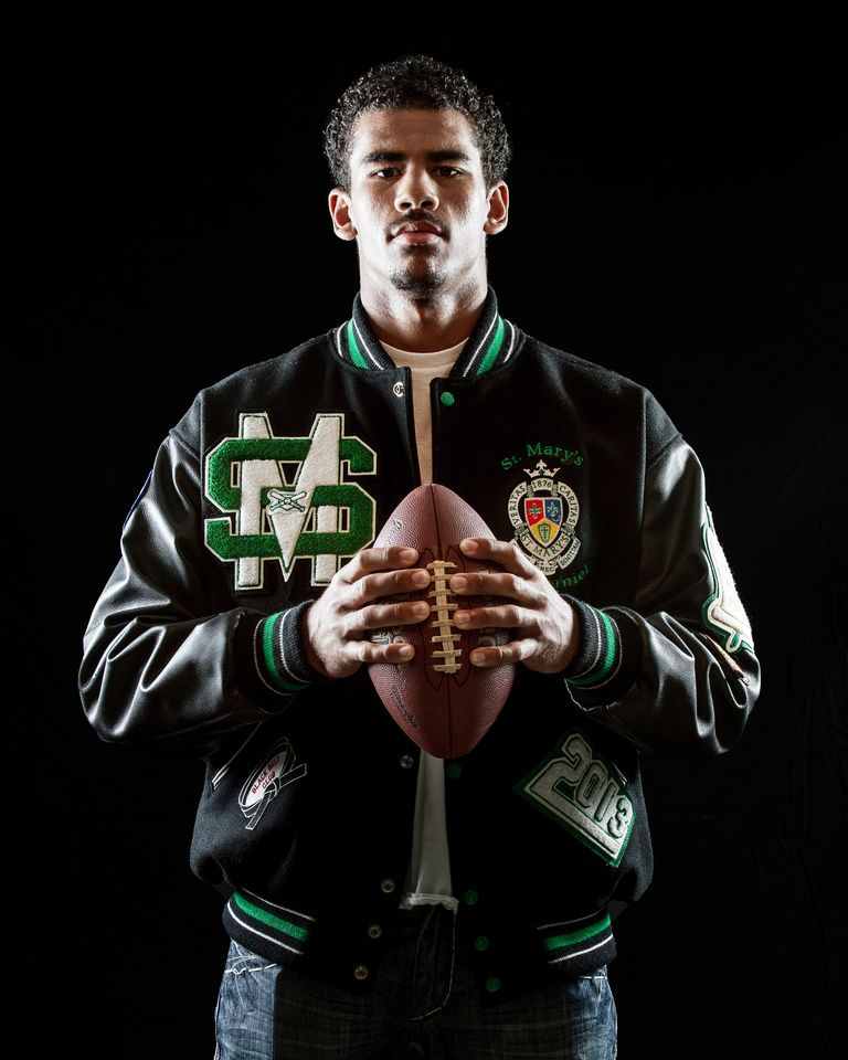 senior portrait with letterman jacket and football