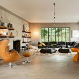 Una sala amplia con ventanales, sofá negro con cojines en suelo, alfombra blanca, silla narajada, repisas en la pared.